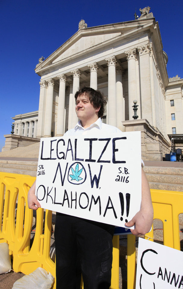 Photo - Adam Dryden, Norman, holds a sign in support of Senate Bill 2116 to legalize marijuana during a rally on the south steps of the state Capitol in Oklahoma City Wednesday, Feb. 12, 2014.  Supporters converged on the state Capitol to personally lobby their legislators to reform Oklahoma's strict marijuana laws during