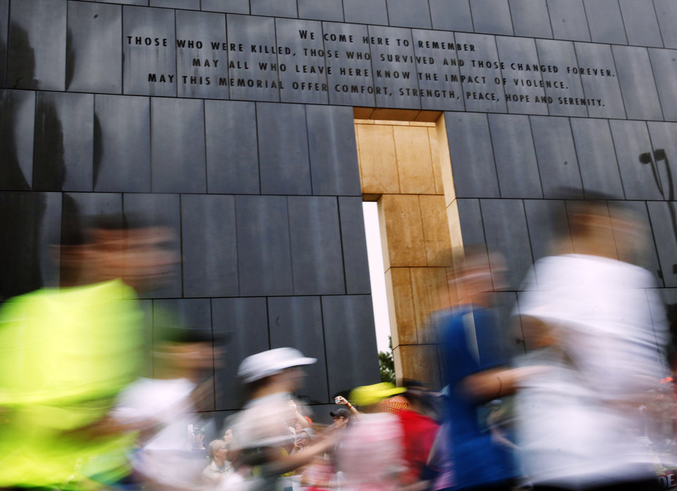 Photo - Runners run in front of the 9:03 Gate of Time at the beginning of the 14th Annual Oklahoma City Memorial Marathon in Oklahoma City, Sunday, April 27, 2014. The marathon was delayed over two hours beyond it's original start time of 6 a.m. Photo by KT King/The Oklahoman