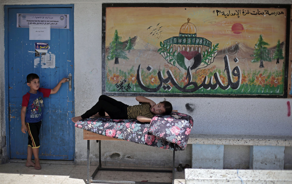 Photo - A Palestinian girl rests next to a painting with Arabic writing that reads