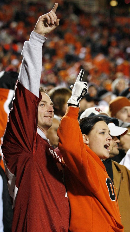 OU fan Rich Hibbs and OSU fan Savannah Marvin cheer during the second half of the college football game between the University of Oklahoma Sooners (OU) and Oklahoma State University Cowboys (OSU) at Boone Pickens Stadium on Saturday, Nov. 29, 2008, in Stillwater, Okla. STAFF PHOTO BY NATE BILLINGS