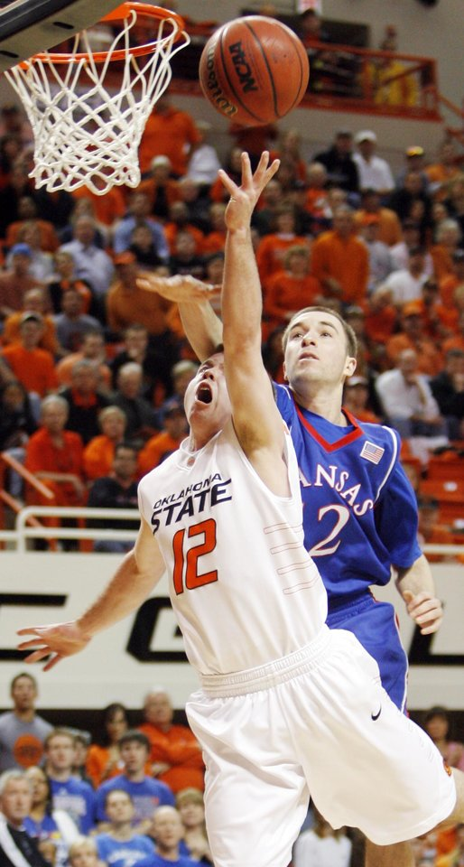 Photo - OSU's Keiton Page (12) is fouled by Brady Morningstar (12) of KU in the first half during the men's college basketball game between the University of Kansas (KU) and Oklahoma State University (OSU) at Gallagher-Iba Arena in Stillwater, Okla., Saturday, Feb. 27, 2010. Page made this basket and the foul shot. Photo by Nate Billings, The Oklahoman