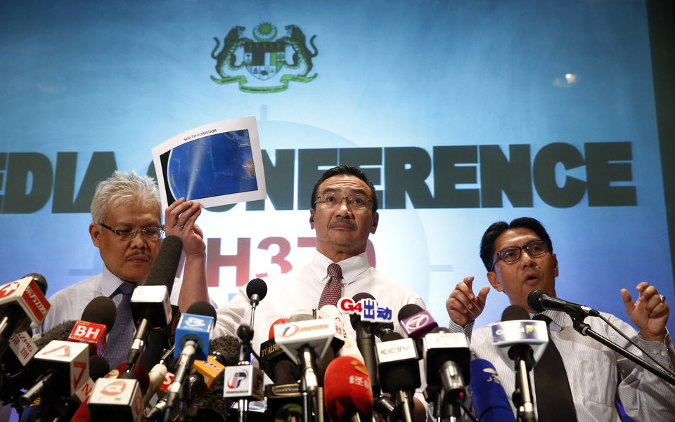Photo - Malaysian acting Transport Minister Hishamuddin Hussein, center, shows maps of South Corridor and North Corridor of the search and rescue as director general of the Malaysian Department of Civil Aviation, Azharuddin Abdul Rahman, right, and Malaysian Deputy Foreign Minister Hamzah Zainudin during a press conference at a hotel next to the Kuala Lumpur International Airport, in Sepang, Malaysia, Monday, March 17, 2014. The search for the missing Malaysian jet pushed deep into the northern and southern hemispheres Monday as Australia took the lead in scouring the seas of the southern Indian Ocean and Kazakhstan - about 10,000 miles to the northwest - answered Malaysia's call for help in the unprecedented hunt. (AP Photo/Vincent Thian)