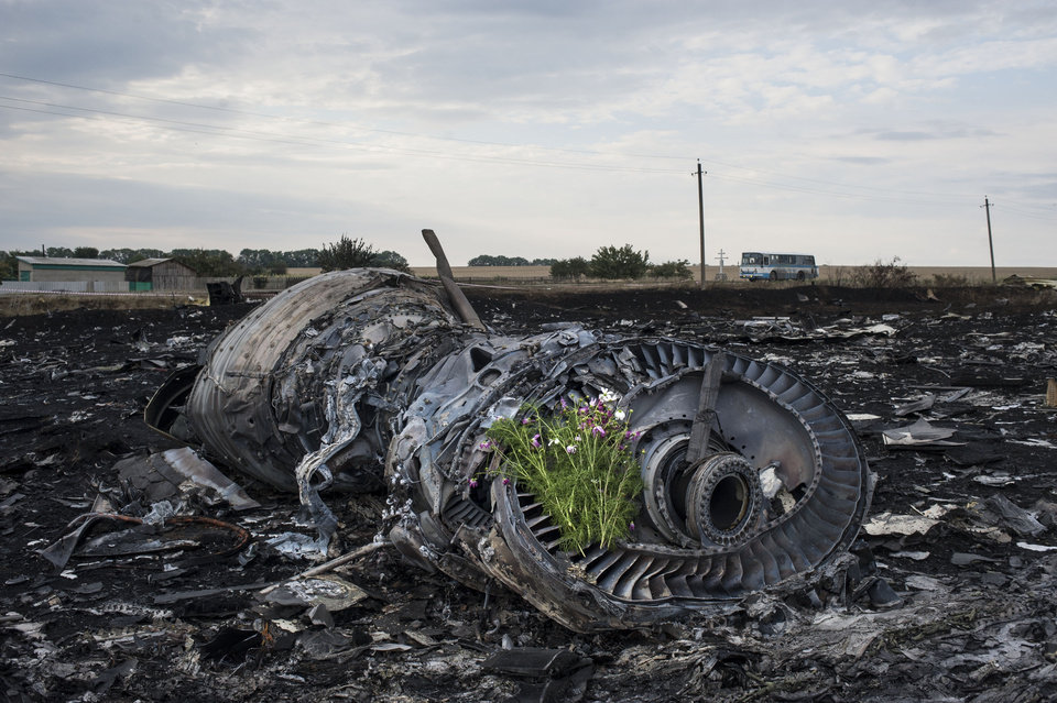 Photo - Flowers are placed on a plane engine at the crash site of a Malaysia Airlines jet near the village of Hrabove, eastern Ukraine, Saturday, July 19, 2014. World leaders demanded Friday that pro-Russia rebels who control the eastern Ukraine crash site of Malaysia Airlines Flight 17 give immediate, unfettered access to independent investigators to determine who shot down the plane. (AP Photo/Evgeniy Maloletka)