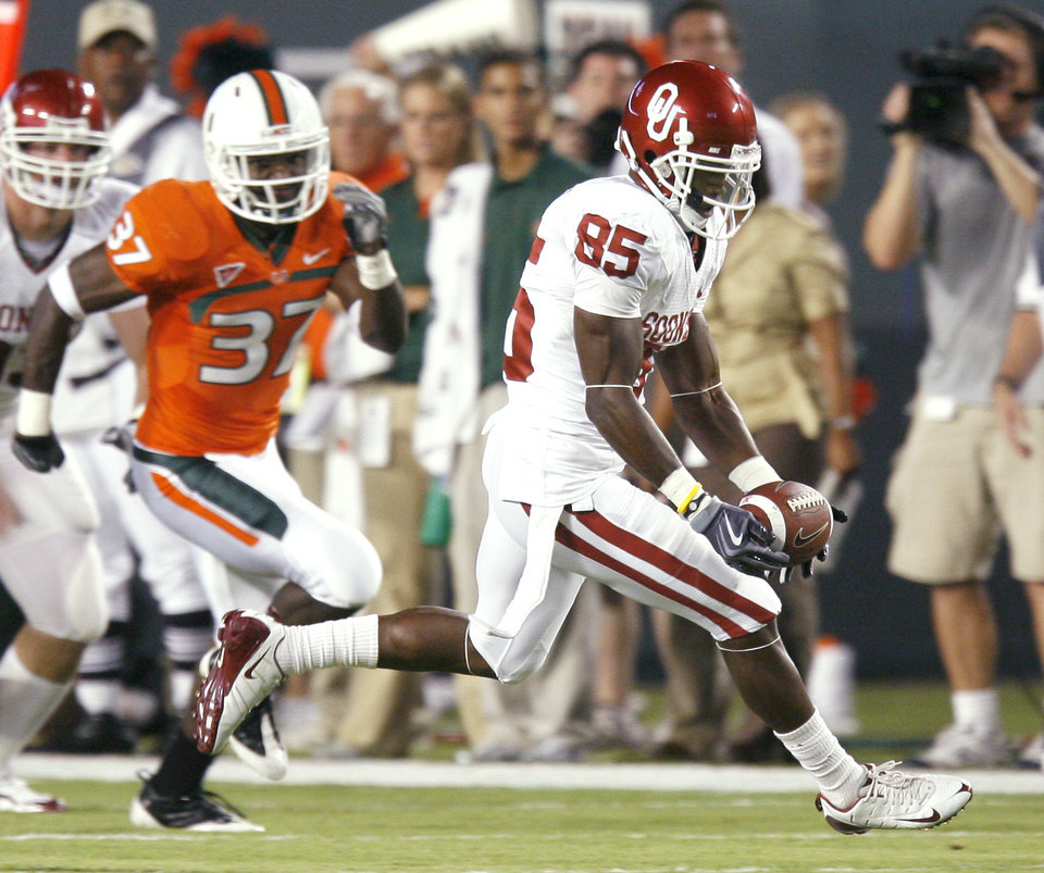 Photo - OU's Ryan Broyles brings in a reception in front of Miami's Jared Campbell during the college football game between the University of Oklahoma (OU) Sooners and the University of Miami (UM) Hurricanes at Land Shark Stadium in Miami Gardens, Florida, Saturday, October 3, 2009. Photo by Bryan Terry, The Oklahoman ORG XMIT: KOD