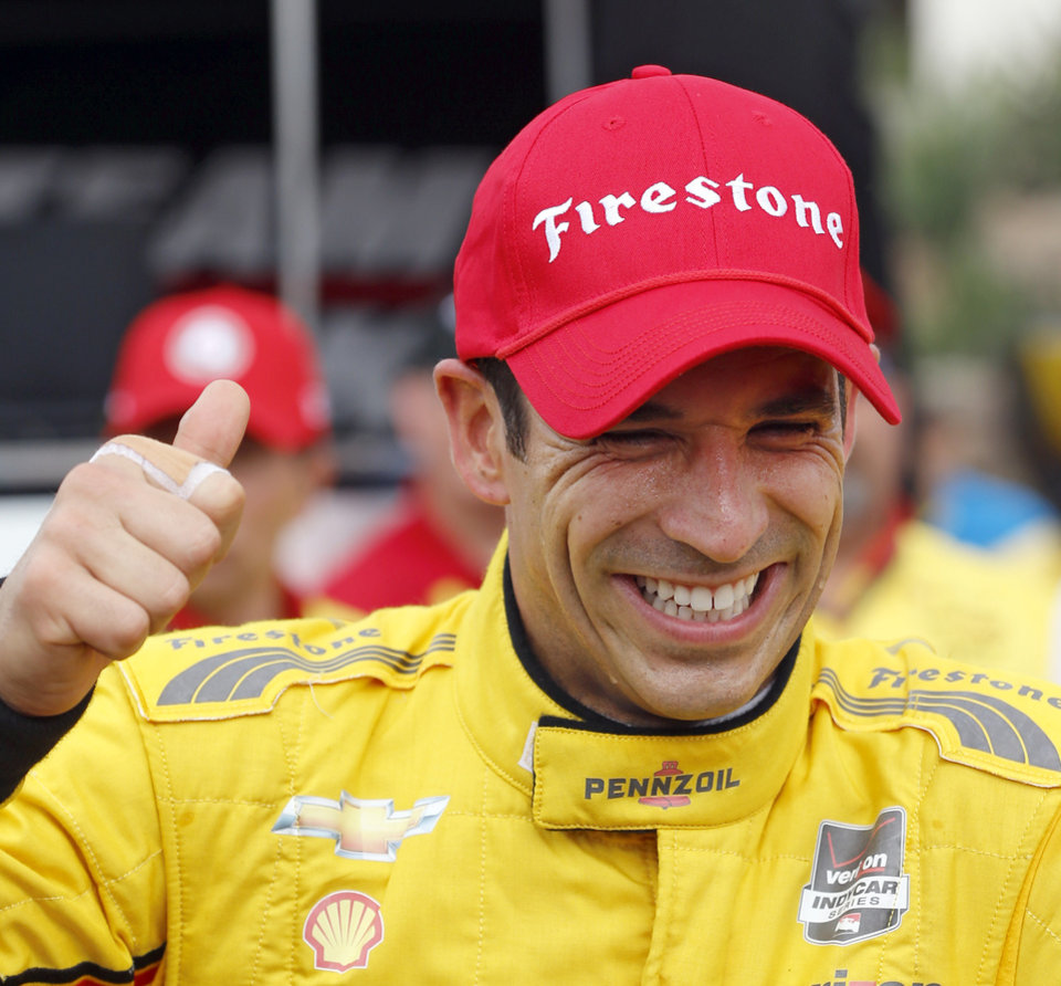 Photo - Helio Castroneves, of Brazil, reacts after winning qualifying and the pole position for the second IndyCar Grand Prix of Houston auto race Sunday, June 29, 2014, in Houston. (AP Photo/David J. Phillip)