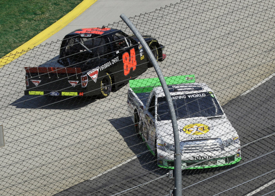 Driver Grant Galloway (07) spins out in front of Robert Bruce (84) during the Kroger 250 NASCAR Truck series auto race at Martinsville Speedway, Saturday, April 6, 2013, in Martinsville, Va. (AP Photo/Steve Helber)