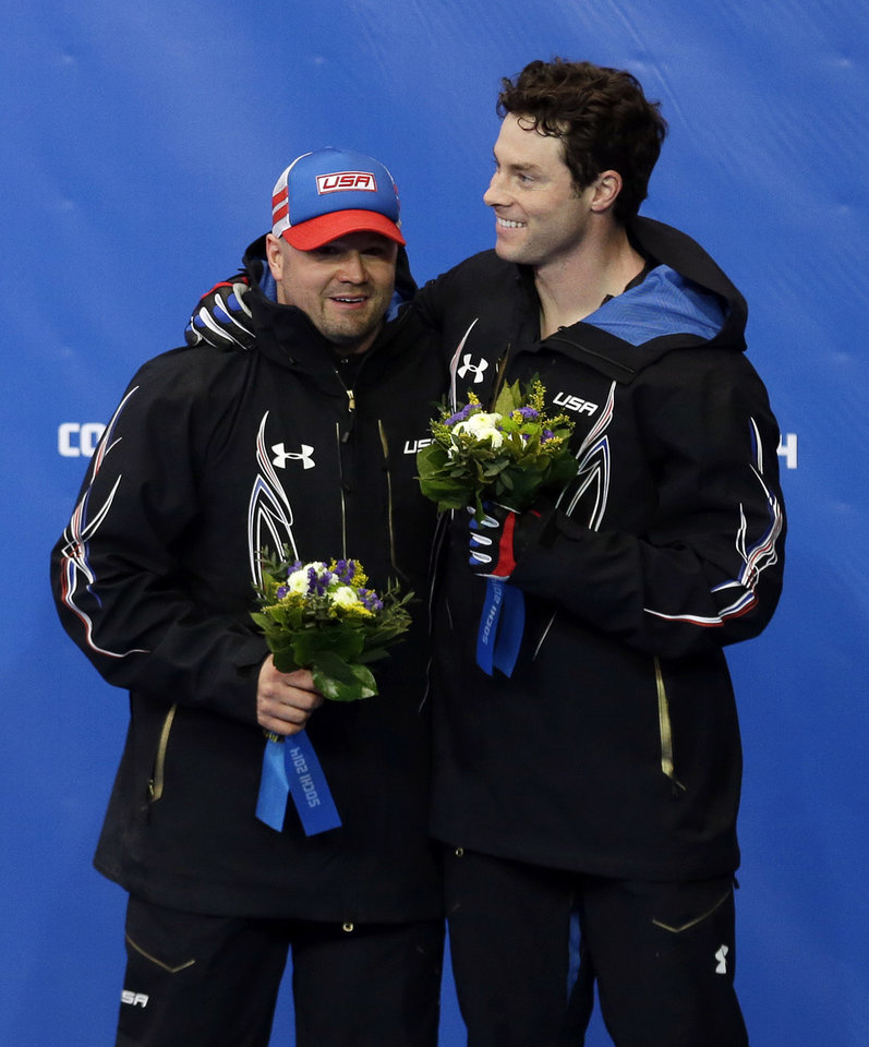 Photo - The team from the United States USA-1, piloted by Steven Holcomb, left, and brakeman Steven Langton, celebrate their bronze medal win after the men's two-man bobsled competition at the 2014 Winter Olympics, Monday, Feb. 17, 2014, in Krasnaya Polyana, Russia. (AP Photo/Natacha Pisarenko)