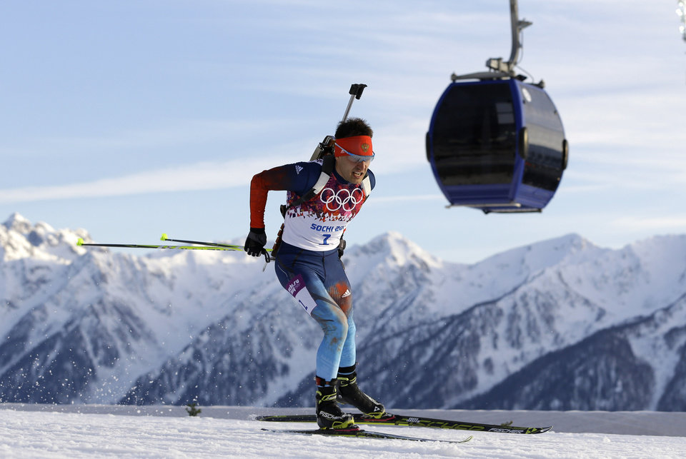 Photo - Russia's Yevgeny Garanichev skis past a gondola during the men's biathlon 20k individual race, at the 2014 Winter Olympics, Thursday, Feb. 13, 2014, in Krasnaya Polyana, Russia. (AP Photo/Kirsty Wigglesworth)
