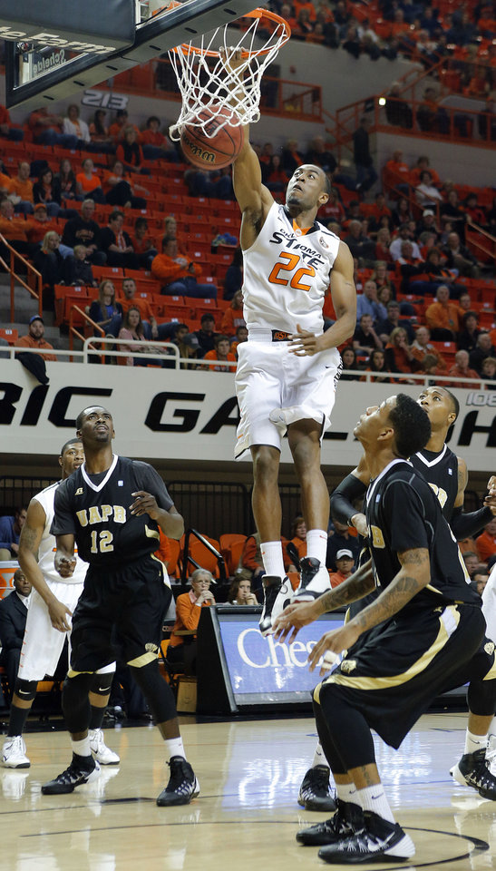 Photo - Oklahoma State's Markel Brown (22) dunks over the Arkansas-Pine Bluff defense at the college basketball game between the Oklahoma State University Cowboys (OSU) and the University of Arkansas Pine Bluff Golden Lions at Gallagher Iba Arena in Stillwater, Okla. on Friday, Nov. 15, 2013. Photo by Chris Landsberger, The Oklahoman