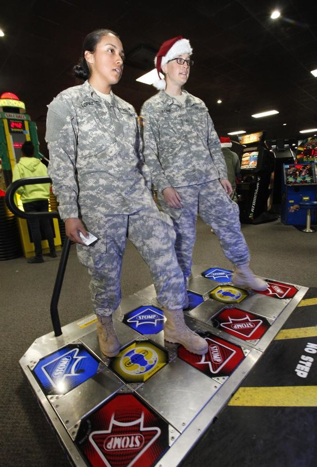New recruits Pvt Diana Lopez and Hillary Bayne play a dance game during a lunch stop at Gatti Town during Soldiers Day Out, Friday, December 21, 2012. Edmond/North OKC Blue Star Mothers will be taking the soldiers who can't go home for Christmas around the metro for a day of fun. Photo By David McDaniel/The Oklahoman