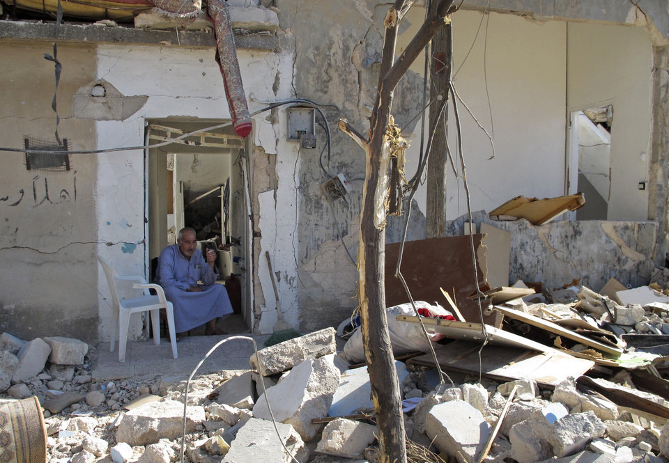 Photo -   Syrian Mahmoud Jikar sits at the door of his house, which was destroyed in a Syrian government bombing last week that killed more than 40 people, in Azaz, Syria, on Monday, Aug. 20, 2012. (AP Photo/Ben Hubbard)