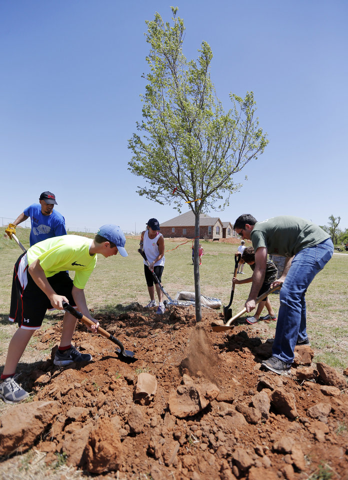 Photo -  Youths and parents from the Inter-Congregational Sunday School of Temple B'nai Israel and Emanuel Synagogue plant trees on property damaged by the May 20 tornado in the south Oklahoma City and Moore areas. Photo by Nate Billings, The Oklahoman   NATE BILLINGS