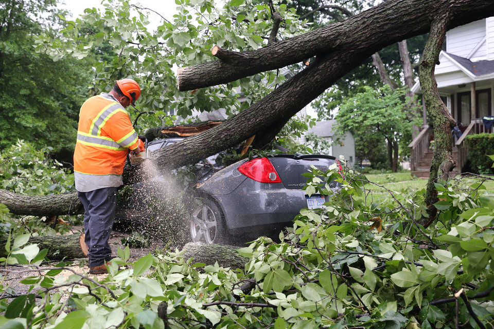 Photo - Clean up crews work to remove fallen trees after a storm in Vicksburg, Mich., Tuesday, July 1, 2014. Severe thunderstorms packing high winds knocked down trees and power lines across parts of Michigan, leaving more than 230,000 without power and injuring a firefighter. (AP Photo/Kalamazoo Gazette-MLive Media Group, Mark Bugnaski) ALL LOCAL TELEVISION OUT; LOCAL TELEVISION INTERNET OUT
