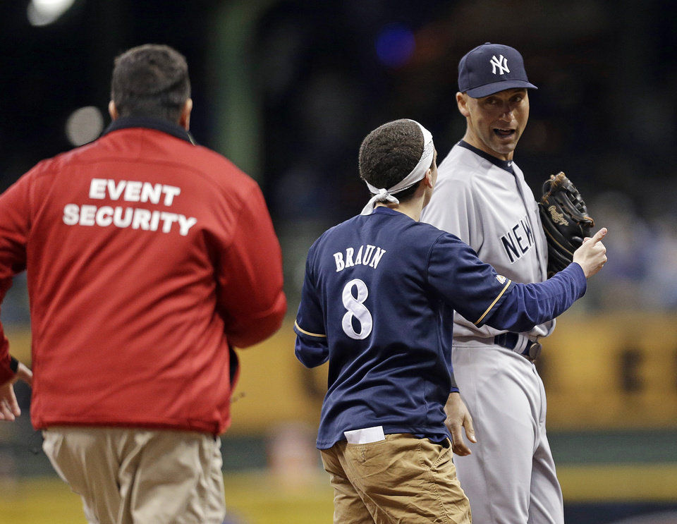 A fan runs out on the field to New York Yankees\' Derek Jeter, right, in the sixth inning of a baseball game against the Milwaukee Brewers, Friday, May 9, 2014, in Milwaukee. (AP Photo/Jeffrey Phelps)