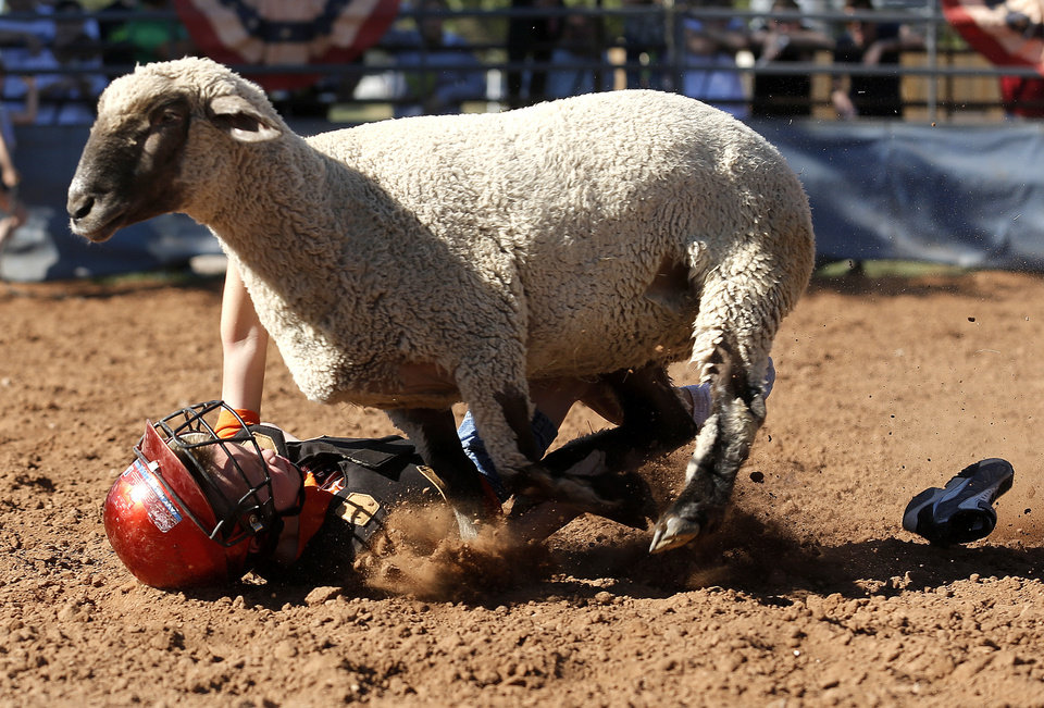 Photo - Joe Nanney falls to the ground during a mutton bustin at the last day of the Oklahoma State Fair in Oklahoma City, Sunday, Sept. 22, 2013. Photo by Sarah Phipps, The Oklahoman