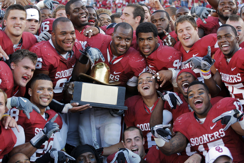 Photo - The Sooners pose for a photo with the Golden Hat trophy after the Red River Rivalry college football game between the University of Oklahoma Sooners (OU) and the University of Texas Longhorns (UT) at the Cotton Bowl on Saturday, Oct. 2, 2010, in Dallas, Texas. OU won, 28-20. Photo by Nate Billings, The Oklahoman
