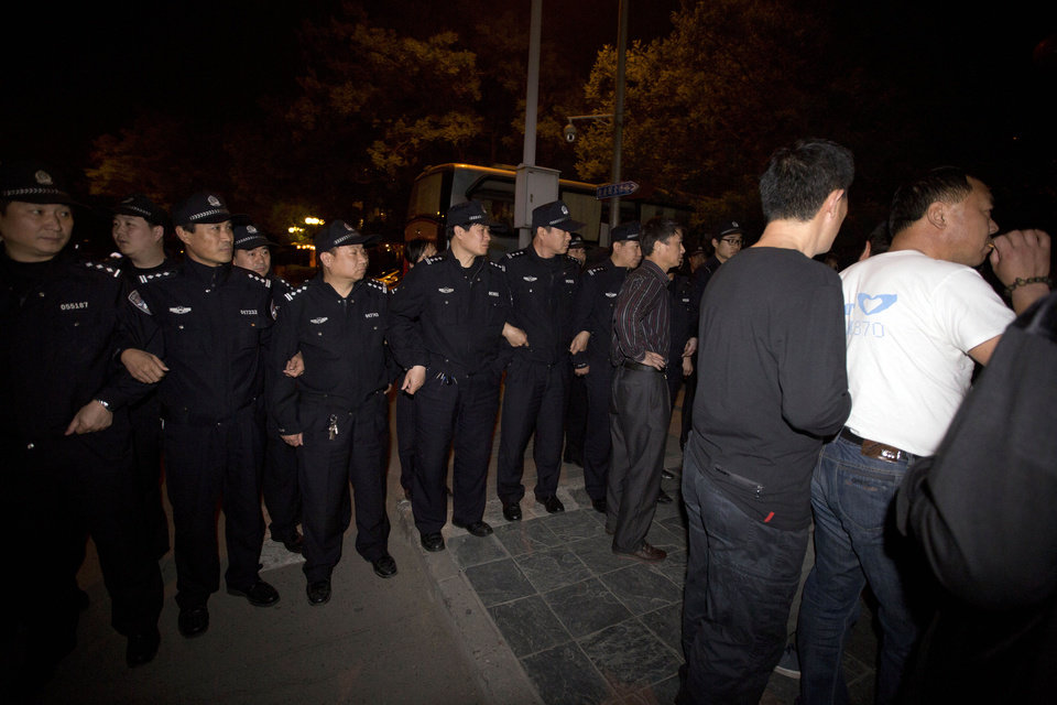 Photo - Chinese police men lock arms to prevent relatives of Chinese passengers onboard the Malaysia Airlines MH370 from marching to the Malaysian embassy from a hotel in Beijing, China, Thursday, April 24, 2014. Angry relatives who had been waiting for more than 8 hours in vain for a Malaysia embassy representative to attend their daily meetings marched to the Malaysia embassy and protested through the night. (AP Photo/Ng Han Guan)