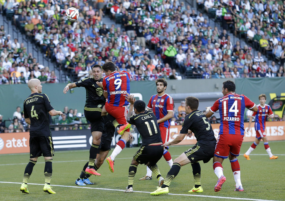 Photo - Seattle Sounders midfielder Clint Dempsey, second from left, and Bayern Munich's Robert Lewandowski (9) vie for the ball in the first half of the MLS All-Star soccer game, Wednesday, Aug. 6, 2014, in Portland, Ore. (AP Photo/Ted S. Warren)