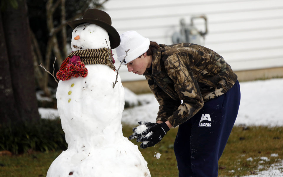 Photo - Parker Alexander, 14, puts the finishing touches on a snowman he and his sister Molly built in the front yard of their Jackson, Miss., home Thursday,  Jan. 17, 2013.  A winter storm system left 2 to 4 inches of snow in parts of central Mississippi before heading east toward Alabama, the National Weather Service said. (AP Photo/Rogelio V. Solis)