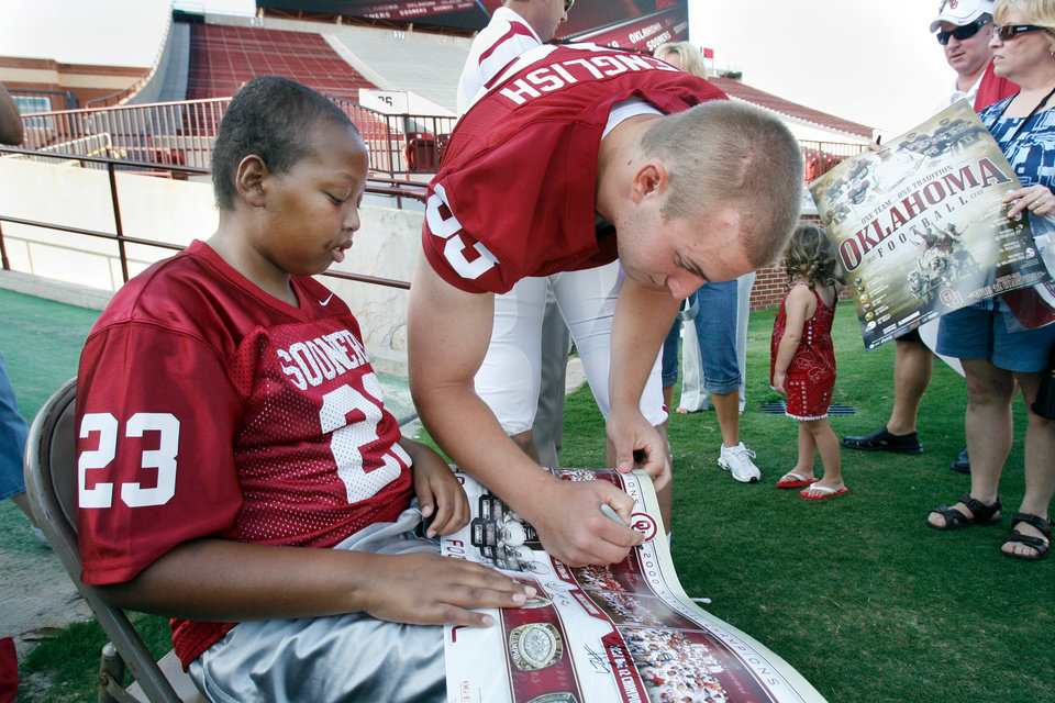 Photo - OU COLLEGE FOOTBALL: Auston English signs a poster for David Haywood, 12, during Media Day for the University of Oklahoma football team at Gaylord Family -- Oklahoma Memorial Stadium in Norman, Oklahoma on Wednesday, August 6, 2008.   BY STEVE SISNEY, THE OKLAHOMAN    ORG XMIT: KOD