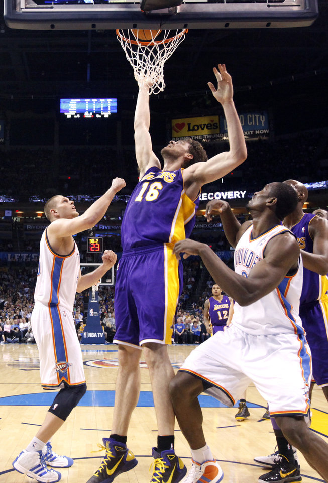 Photo - Lakers' Pau Gasol (16) tips the ball in as Oklahoma City's Oklahoma City's Cole Aldrich (45) and Serge Ibaka (9) defend during the NBA basketball game between the Oklahoma City Thunder and the Los Angeles Lakers, Sunday, Feb. 27, 2011, at the Oklahoma City Arena.Photo by Sarah Phipps, The Oklahoman