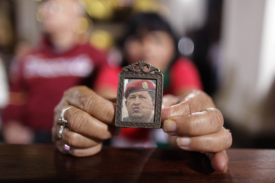 "A woman holds an image of Venezuela's President Hugo Chavez as people gather to pray for him at a church in Caracas, Venezuela, Monday, Dec. 31, 2012. Venezuela's President Hugo Chavez is confronting ""new complications"" due to a respiratory infection nearly three weeks after undergoing cancer surgery, his Vice President Nicolas Maduro said Sunday evening in Cuba as he visited the ailing leader for the first time since his operation. (AP Photo/Ariana Cubillos)"