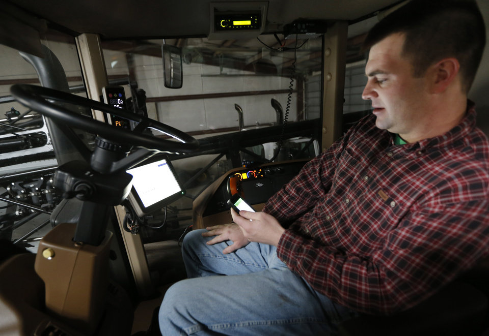 Photo - Nick Guetterman looks over the data shared by his crop sprayer and cell phone while on his farm near Bucyrus, Kan., Wednesday, Feb. 19, 2014.  Farmers from across the nation gathered in Washington this month for their annual trek to seek action on the most important matters in American agriculture.  But this time, a new issue emerged: growing unease about how the largest seed companies are gathering vast amount of data from sensors on tractors, combines and other farm equipment. The sensors measure soil conditions, seeding rates, crop yields and many other variables.  (AP Photo/Orlin Wagner)