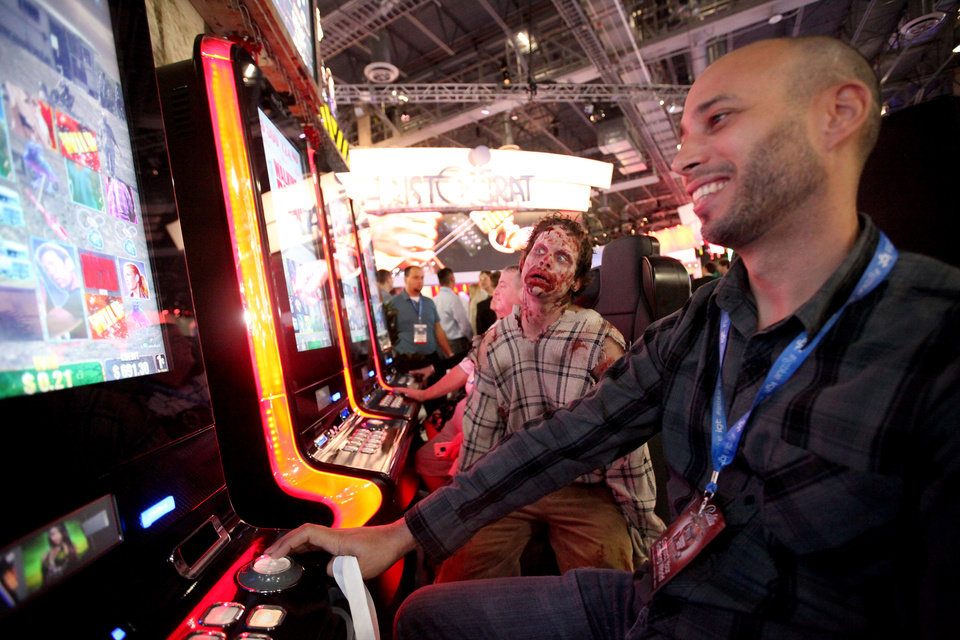 """Photo - """"Zombie"""" Mike Pearson III, left, of Las Vegas, watches as software developer Tony Bennett of Austin, Texas plays The Walking Dead machines at the G2E convention in Las Vegas Tuesday, Sep. 24, 2013. The Aristocrat show floor had more than one zombie roaming to promote The Walking Dead. (AP Photo/Las Vegas Review-Journal, Jessica Ebelhar) LOCAL TV OUT; LOCAL INTERNET OUT; LAS VEGAS SUN OUT ORG XMIT: NVLAS101"""