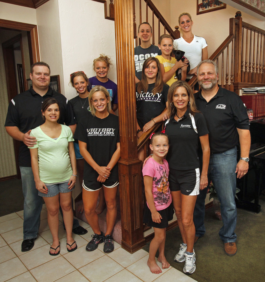 Allyson Reneau and husband Dale Jr. (bottom right with youngest daughter Julianne, 6,) at home with her family on Thursday, August 25, 2011, in Norman and Oklahoma City, Okla. Family left to right are Dale and his wife Ashley, Cindie, Christie, Olympia (left of post) and Kimberly (top), Ashlyne, Sydnie and Victory. Photo by Steve Sisney, The Oklahoman