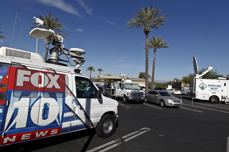 Photo - Television trucks park next to at a 4 Sons Food Store where one of the winning tickets in the $579.9 million Powerball jackpot was purchased, Nov. 29, 2012, in Fountain Hills, Ariz.(AP Photo/Ross D. Franklin)