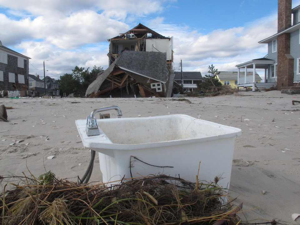 Photo - in an Oct. 31, 2012, photo a kitchen sink sits on the beach in Mantoloking, N.J., two days after Superstorm Sandy devastated the Jersey shore town. Even with federal reimbursement for much of the cleanup and rebuilding expenses, hard-hit towns could be facing property tax hikes next year as a result of the unexpected costs, and the loss of millions of dollars of taxable property. (AP Photo/Wayne Parry)