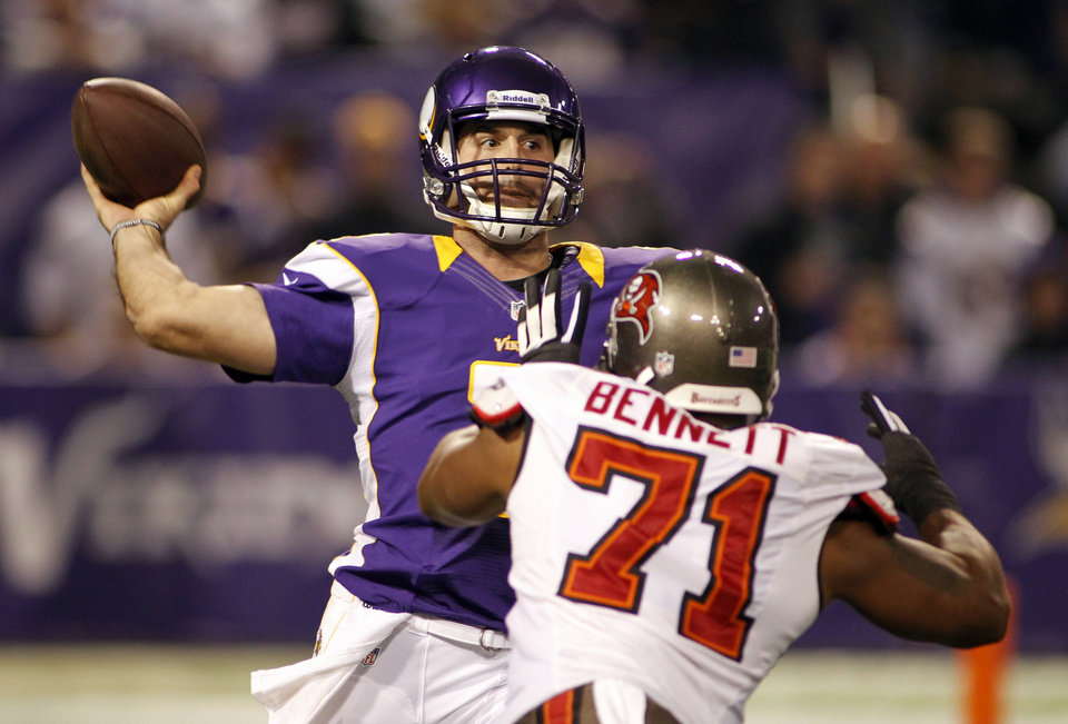 Photo -   Minnesota Vikings quarterback Christian Ponder, left, throws a pass over Tampa Bay Buccaneers defensive end Michael Bennett during the first half of an NFL football game Thursday, Oct. 25, 2012, in Minneapolis. (AP Photo/Andy King)