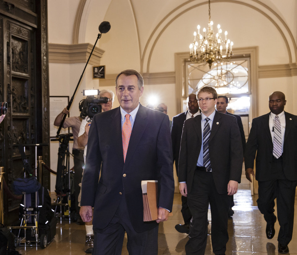 Photo - Speaker of the House John Boehner, R-Ohio, arrives at the Capitol in Washington, Saturday, Oct. 5, 2013. The Republican-controlled House and the Democrat-controlled Senate are at an impasse, neither side backing down, after House GOP conservatives linked the funding bill to President Obama's existent health care law. There has been no sign of progress toward ending the government shutdown that has idled 800,000 federal workers and curbed services around the country.  (AP Photo/J. Scott Applewhite)
