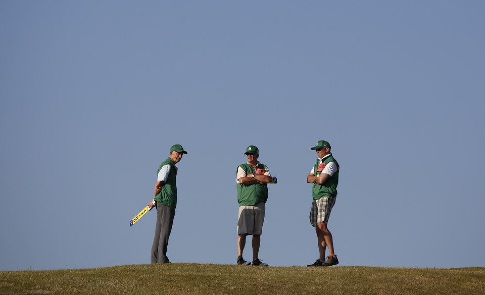 Course marshals stand on a hill on the 13th hole during the second round of the British Open Golf Championship at Muirfield, Scotland, Friday July 19, 2013. (AP Photo/Matt Dunham)