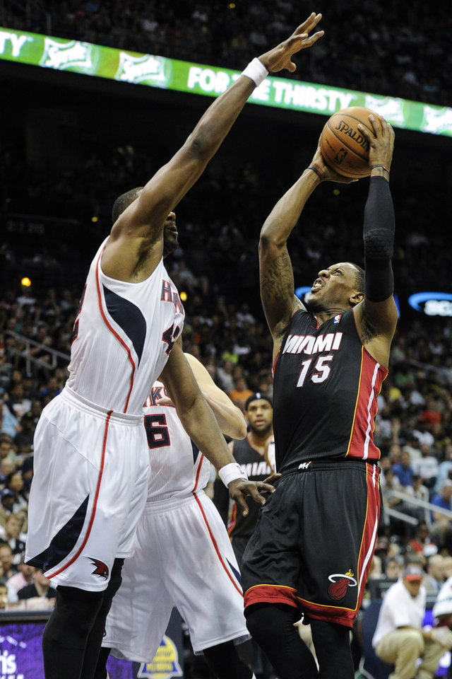 Photo - Miami Heat guard Mario Chalmers (15) shoots against the defense of Atlanta Hawks forward Elton Brand, left, during the first half of an NBA basketball game on Saturday, April 12, 2014, in Atlanta. (AP Photo/John Amis)