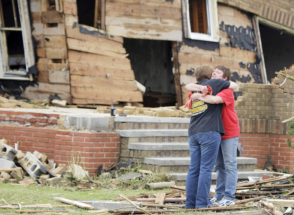 Stephanie Wilson, left, and Wanda Whyte hug Tuesday outside of the tornado-damaged home of Whyte's in-laws in Joplin, Mo. AP Photo
