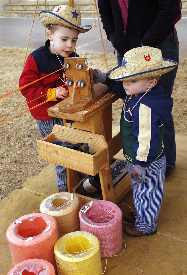 "Brothers Kian Corry, 4, left, and Larkin, 2 1/2, of Midwest City, wait for instructions so they can make a section of braided rope on this special machine. Children with their parents endured cold temperatures and intermittent rain to come to the grounds of the Oklahoma History Center on Saturday, March 23, 2013, to participate in the 3rd annual Cowboy Round-up,  billed to be a  ""rendezvous with adventure.""  Cowboys and chuck wagons were on hand to bring the cattle drive era to life for visitors of all ages. Special activities included pony rides, stick-horse races, roping demonstrations, branding,  a medicine man show, biscuits made from scratch and cooked in Dutch ovens, and a chance for children to make a braided rope they could take with them as a souvenir.  Youth were encouraged to dress the part as many did, wearing boots, vests, bandanas, chaps,and cowboy hats.    Photo by Jim Beckel, The Oklahoman"