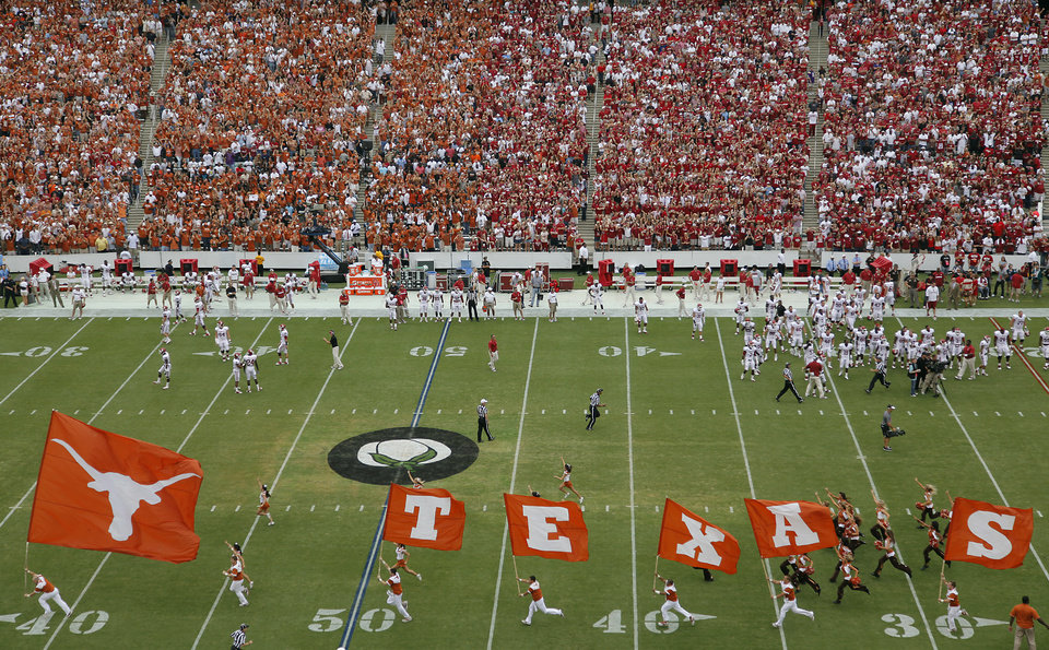 Photo - The Texas Longhorns run onto the field during the Red River Rivalry college football game between the University of Oklahoma Sooners (OU) and the University of Texas Longhorns (UT) at the Cotton Bowl in Dallas, Saturday, Oct. 8, 2011. Photo by Chris Landsberger, The Oklahoman