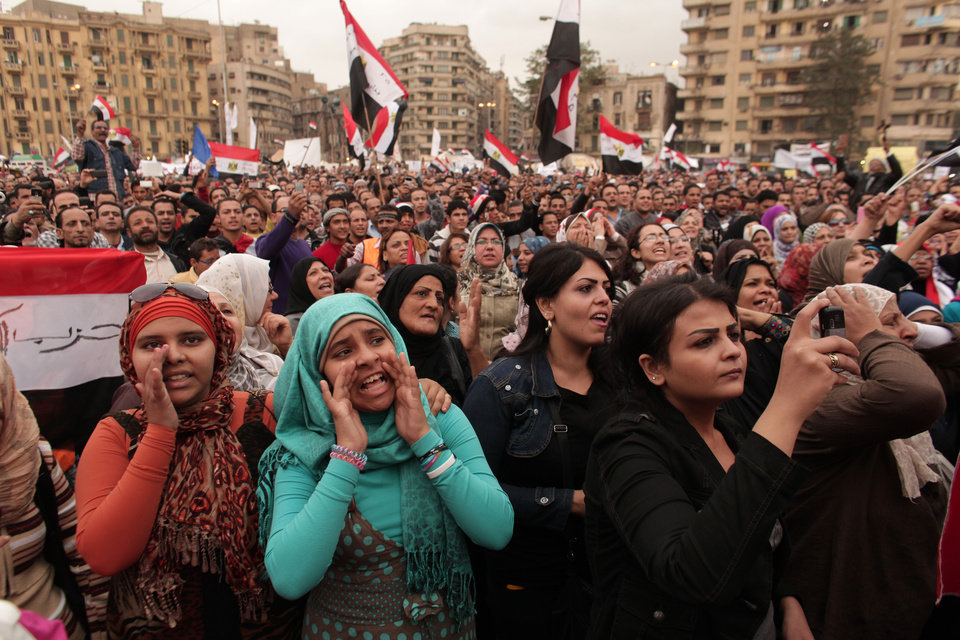 Photo - Protesters chant slogans and wave national flags in Tahrir Square in Cairo, Egypt, Tuesday, Dec. 4, 2012. Hundreds of black-clad riot police deployed around the Itihadiya palace in Cairo's district of Heliopolis. Barbed wire was also placed outside the complex, and side roads leading to it were blocked to traffic. Protesters gathered at Cairo's Tahrir square and several other points not far from the palace to march to the presidential complex. (AP Photo/Maya Alleruzzo)