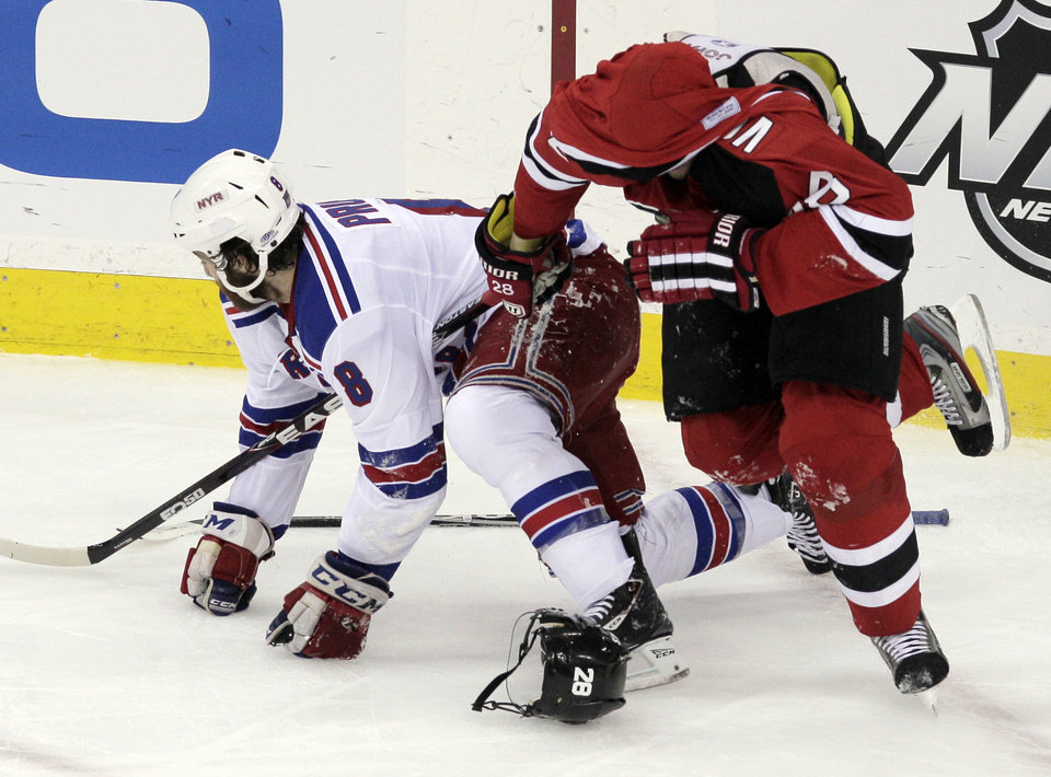 Photo -   New Jersey Devils defenseman Anton Volchenkov, right, of Russia, skates away with his jersey over his head after tussling with New York Rangers right wing Brandon Prust during the first period of game 3 of an NHL hockey Stanley Cup Eastern Conference final playoff series, Saturday, May 19, 2012, in Newark, N.J. (AP Photo/Peter Morgan)