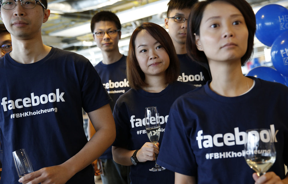 Photo - FILE - In this July 24, 2014 file photo, Facebook staff members attend the opening ceremony of their new office in Hong Kong. Facebook already gets 55 percent of its revenue overseas, and the growth in those markets is outpacing by what's happening in the U.S. The social networking service has attracted 1.1 billion users in foreign markets versus 200 million in the U.S. and Canada. (AP Photo/Kin Cheung, File)