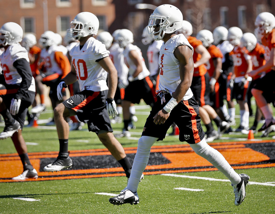 Photo - Oklahoma State players go through warmup drills during the first day of spring practice on Monday in Stillwater.                    Photo by Chris Landsberger, The Oklahoman