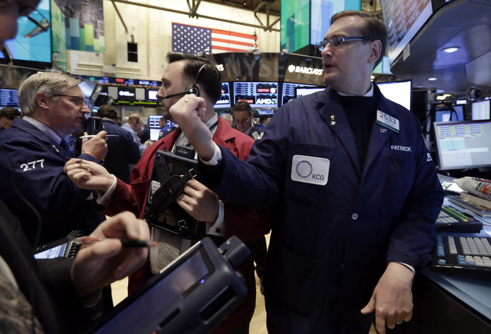 Photo -  Specialist Patrick King, right, works with traders Thursday at his post on the floor of the New York Stock Exchange.  AP Photo   Richard Drew -  AP