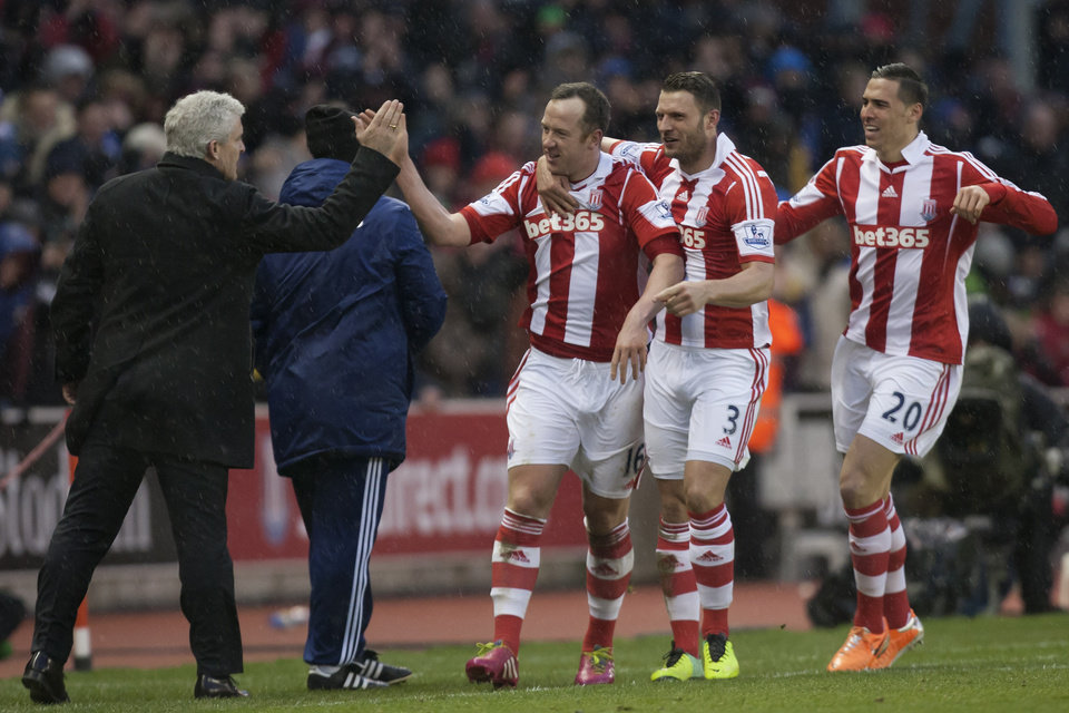 Photo - Stoke's Charlie Adam, centre, celebrates with teammates and manager Mark Hughes, left, after scoring his second goal against Manchester United during their English Premier League soccer match at the Britannia Stadium, Stoke, England, Saturday Feb. 1, 2014. (AP Photo/Jon Super)