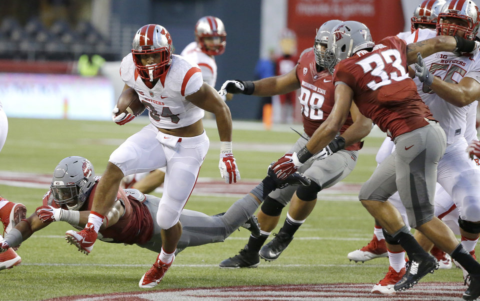 Photo - Rutgers running back Paul James (34) runs the ball as Washington State linebacker Darryl Monroe misses a tackle at lower left in the first half of an NCAA college football game, Thursday, Aug. 28, 2014, in Seattle. (AP Photo/Ted S. Warren)