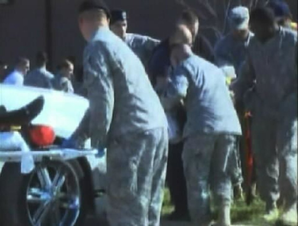 Photo - In this image made from Associated Press Television video, emergency personnel take a wounded person on a stretcher to an awaiting ambulance at the scene at the U.S. Army base in  Fort  Hood Texas where a soldier opened fire, unleashing a stream of gunfire that left at least 12 people dead and at least 31 wounded. Authorities killed the gunman, and apprehended two other soldiers suspected in the attack. (AP Photo/APTN)