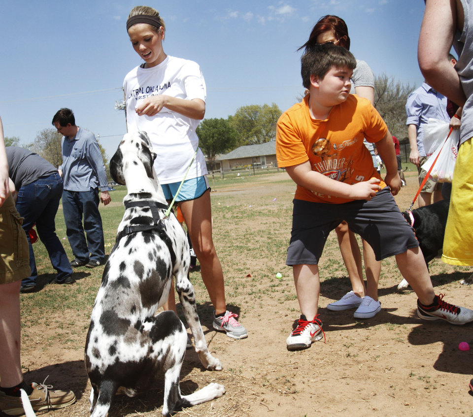 Photo -  Alyssa Mudgett feeds Pearl, her Great Dane, a dog treat from an Easter egg, as one young hunter darts in to steal an egg at the annual Edmond Hound Hunt at Edmond Dog Park. PHOTO BY K.T. King, THE OKLAHOMAN   KT King -