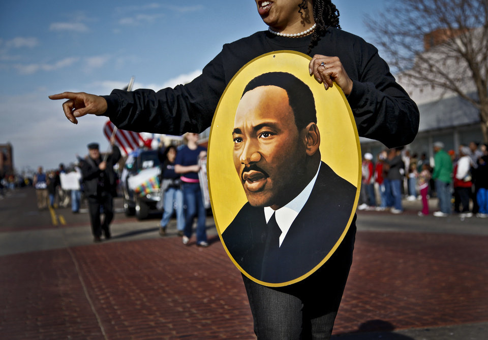 Photo -  State Rep. Anastasia Pittman carries a portrait of Martin Luther King Jr. during the Martin Luther King Jr. parade in downtown on Monday, Jan. 17, 2011, in Oklahoma City, Okla. .    Photo by Chris Landsberger, The Oklahoman