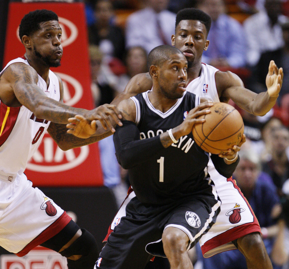 Brooklyn Nets guard C.J. Watson (1) looks for an opening past Miami Heat forward Udonis Haslem, left, and guard Norris Cole during the first half of an NBA basketball game, Wednesday, Nov. 7, 2012, in Miami. (AP Photo/Wilfredo Lee)