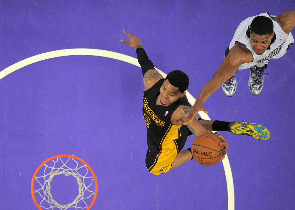 Photo - Los Angeles Lakers guard Kent Bazemore, left, goes up for a dunk as Sacramento Kings forward Rudy Gay defends during the first half of an NBA basketball game, Friday, Feb. 28, 2014, in Los Angeles. (AP Photo/Mark J. Terrill)